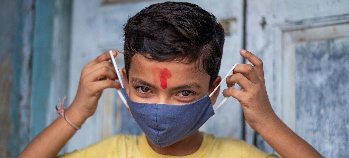 Un niño de 11 años en India muestra cómo ponerse correctamente una máscara para protegerse del COVID-19.