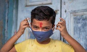 En Inde, un garçon de 11 ans montre la bonne façon de porter un masque.