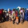 Une Casque bleue du Nigéria avec des femmes et des enfants à la base de la MINUAD, à Labado, dans la région du Darfour, au Soudan.