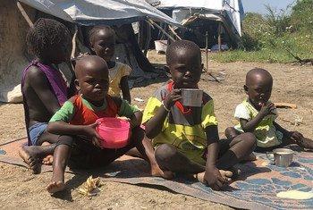 Watoto wakinywa uji uliopikwa na mama yao baada ya kupokea mgao kutoka kwa WFP, Pibor nchini Sudan Kusini.