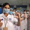 Trabajadores sanitarios posan con una dosis de la vacuna contra el COVID-19. Se necesita aumentar la producción y distribución de vacunas en todo el mundo.