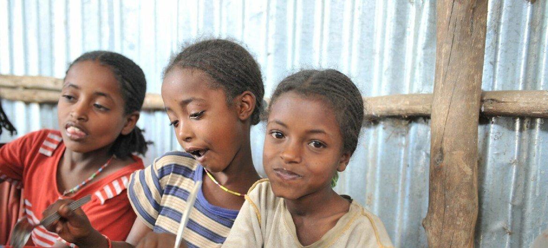 Tres niñas etíopes reciben un almuerzo escolar todos los días en una escuela beneficiada por el PMA.