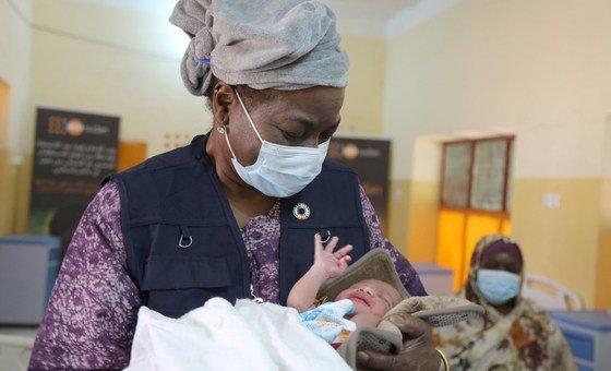 संयुक्त राष्ट्र के जनसंख्या कोष की कार्यकारी निदेशक नतालिया कनेम, सूडान के एक अस्पताल में एक बच्चे को गोद में थामे हुए.
