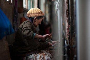 一名移民至印度锡金邦的西藏妇女正在制作织毯。(资料图片)