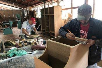 Antiguos combatientes de las FARC trabajan como carpinteros.
