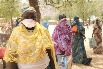 Женщины, стоящие в очереди за продовольственными пайками в Камеруне,  соблюдают социальную дистанцию с тем, чтобы не заразиться коронавирусом