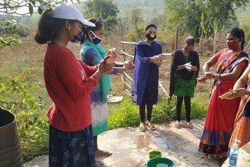 सहकर्मी शिक्षक मालती अपने समुदाय में कोविड सम्बन्धी जागरूकता फैलाने के लिये, लोगों को हाथ धोने की सही तकनीक सिखा रही हैं.