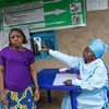 A patient at a health centre in Butembo in the east of the Democratic Republic of the Congo has her temperature measured as part of efforts to prevent the spread of Ebola. (August 2019)