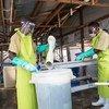 Des employés d'un centre de traitement d'Ebola à Butembo, dans l'est de la RDC, désinfectent leurs bottes et nettoient leurs vêtements.