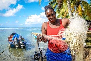 कैरीबियाई द्वीप डोमीनिका में एक महिला मछली पकड़ने के लिये अपना जाल तैयार करते हुए.