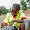 घाना में एक बच्चा खुले स्थान में टायर को मेज़ बनाकर अपनी पढ़ाई करते हुए.