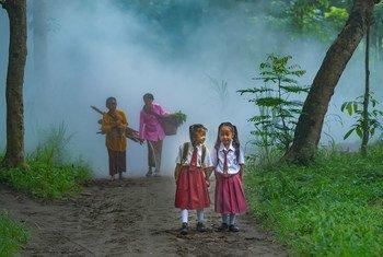 Deux jeunes écolières marchent dans une forêt en Indonésie.