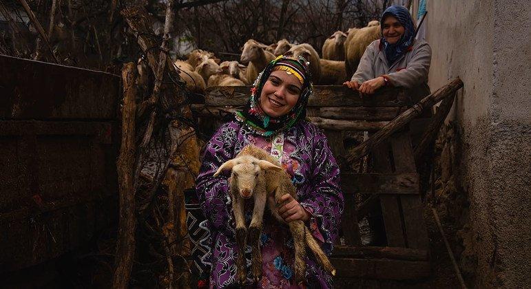 土耳其乡村一名穿着传统服装的妇女抱着她的一只动物。