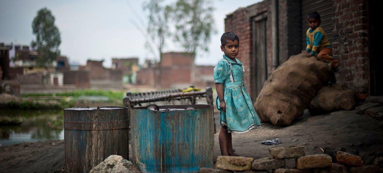 Children play outside a metal polishing workshop in a slum in Uttar Pradesh, India.
