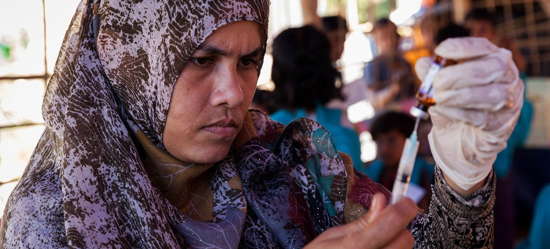 Funcionária de sáude prepara vacina em assentamento de refugiados rohingya em Bangladesh