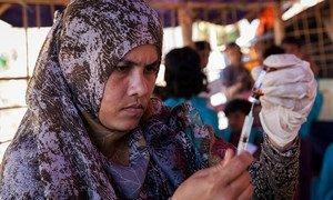 Una trabajadora sanitaria llena una jeringa con una vacuna en un campamento de refugiados rohingya en Cox's Bazar (Bangladesh).