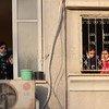 फ़लस्तीनी बच्चे अपनी खिड़की से बाहर क्षतिग्रस्त इमारतों को देख रहे हैं.