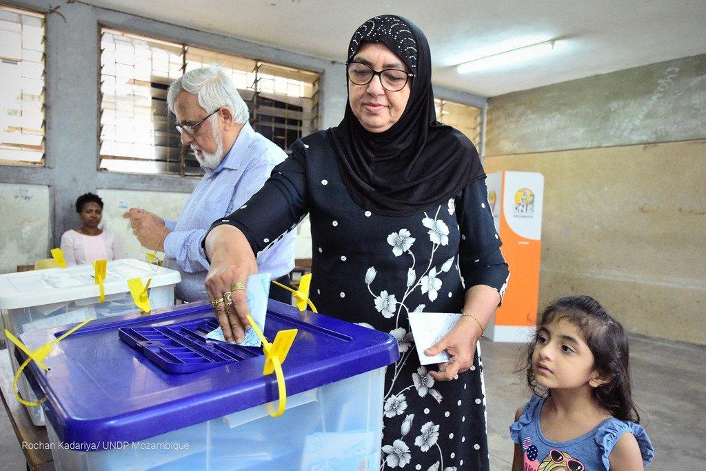 莫桑比克大选期间,一名带着孩子的妇女参加投票。