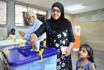 मोज़ाम्बीक़ में आम चुनाव में मतदान करती एक महिला और वोट डालने की प्रक्रिया को देखती एक छोटी बच्ची.
