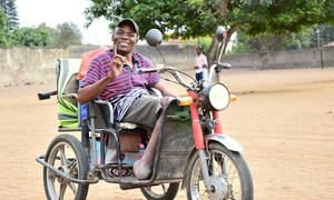 Eleitor moçambicano mostra o dedo com a tinta azul após sair de um local de votação.