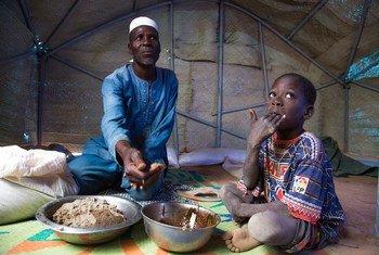 Zore Yusef compartilha uma refeição com um de seus filhos. O conflito armado forçou sua família a fugir da região norte de Burkina Faso.