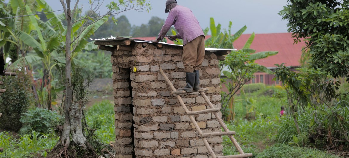 A professional builder constructs a toilet in his community in Burera district, Rwanda. The builder was trained by UNICEF and the NGO Society for Family Health to build hygienic and safe toilets.
