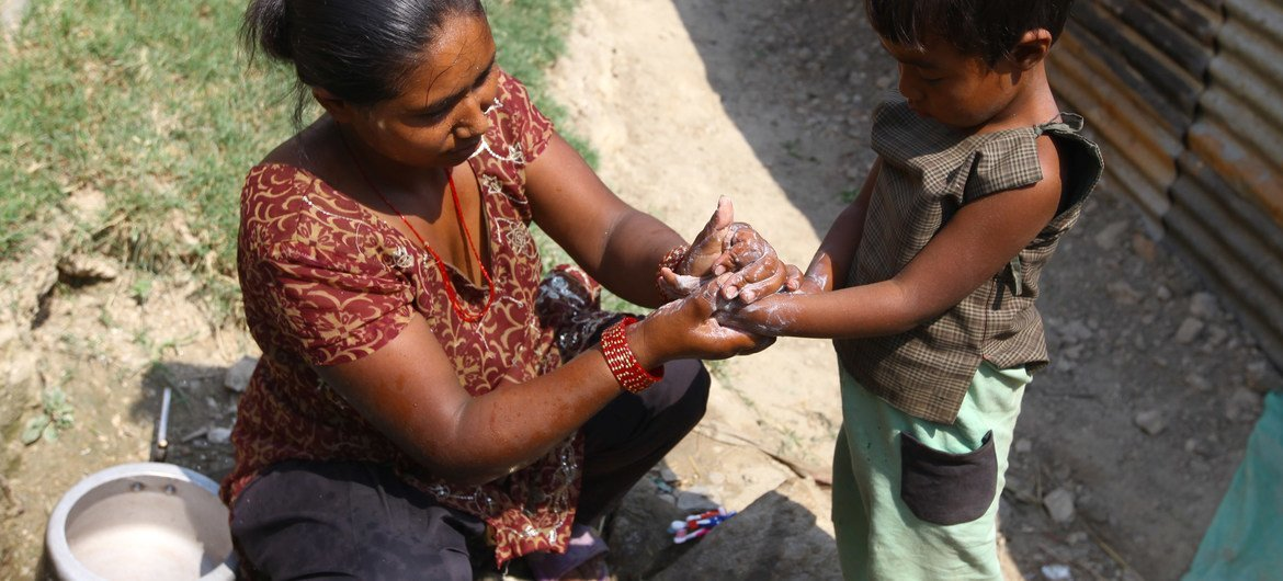 A mother washes her young son's hands with soap in rural Kavre district, Nepal. Proper hand hygiene can help keep many diseases at bay.