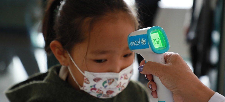 मंगोलिया में एक बच्ची के तापमान की जाँच की जा रही है.