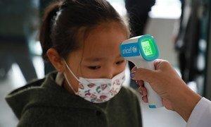 Toman la temperatura a una niña pequeña en Mongolia con un termómetro proporcionado por UNICEF para prevenir los contagios de COVID-19.