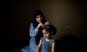Wafaa, une réfugiée syrienne de 32 ans, épingle les cheveux de sa fille Yasmine, âgée de trois ans, chez elles à Barja, au Liban. Elles attendent d'être réinstallées en Norvège.