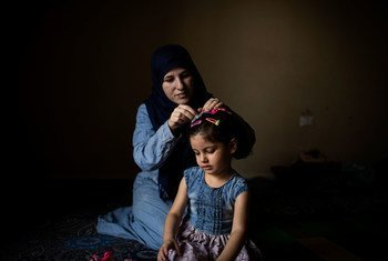 Thirty-two-year-old Syrian refugee Wafaa pins her three-year-old daughter Yasmine's hair at their home in Barja, Lebanon. They are awaiting resettlement to Norway.