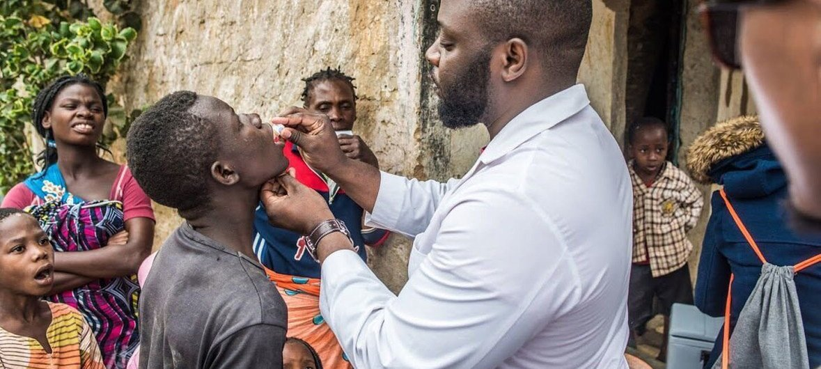 A child is administered an oral vaccine against cholera as part of a large-scale vaccination campaign.