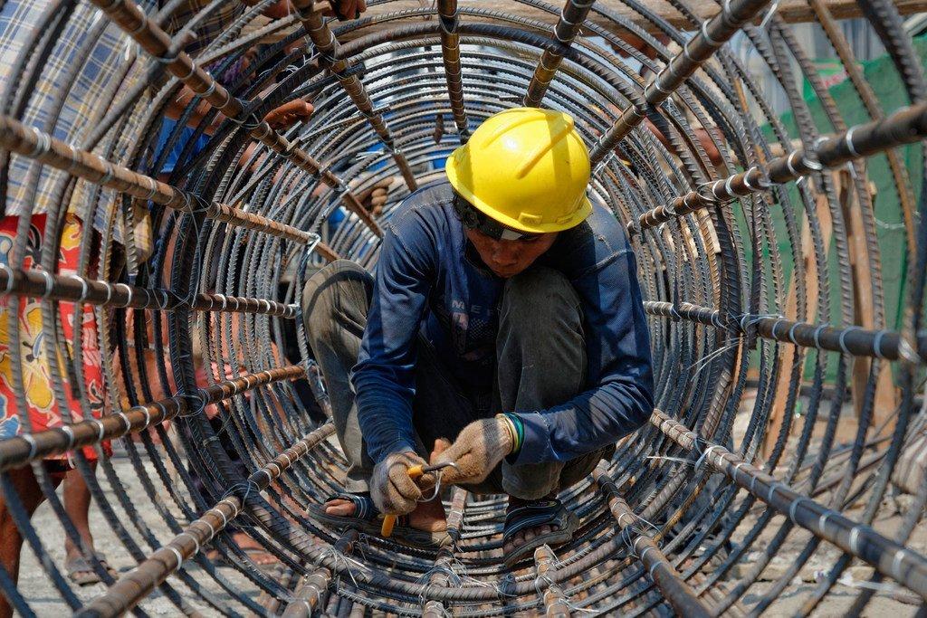 Un ouvrier du bâtiment travaille dans une structure de métal cylindrique à Yangon, au Myanmar.