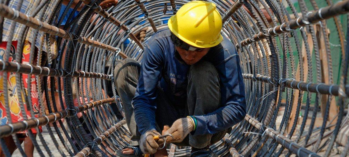 缅甸仰光一名建筑工人正在建造圆柱形金属结构。