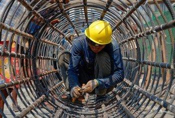 Trabalhador constroi estrutura de metal em Yangon, em Mianmar
