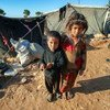 Children stand outside the tent where they live in a remote desert camp in southern rural Homs, Syria.