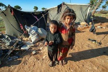 叙利亚霍姆斯南部偏远农村地区的一个营地,孩子们站在帐篷外,周围都是沙地。