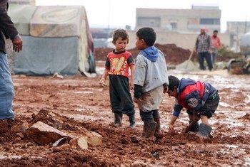 أطفال يلعبون في الوحل في مخيم للنازحين يقع شمال حلب، سوريا.