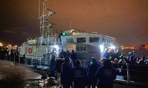 موظفو المنظمة الدولية للهجرة في ليبيا يساعدون المهاجرين في نقطة للنزول في الساحل، طرابلس، ليبيا.