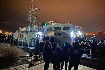 ARCHIVO. Personal de la OIM ayuda a desembarcar a migrantes en Trípoli, Libia
