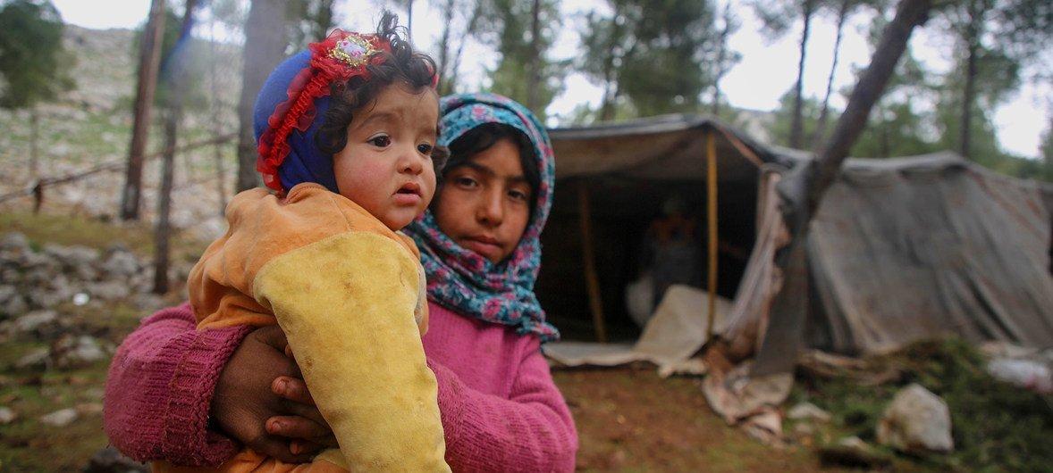 في 7 شباط/فبراير 2020، طفلة تحمل طفلا مع نزوح الأطفال والعائلات من جنوب إدلب وغرب حلب باتجاه المناطق الشمالية من إدلب وحلب في سوريا