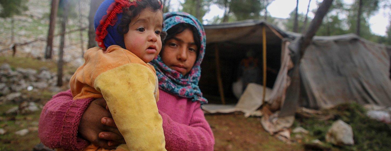 Le 7 février 2020, une fille porte un enfant plus jeune alors que des enfants et leurs familles fuient le sud d'Idlib et l'ouest d'Alep vers la partie nord d'Idlib et d'Alep en Syrie.