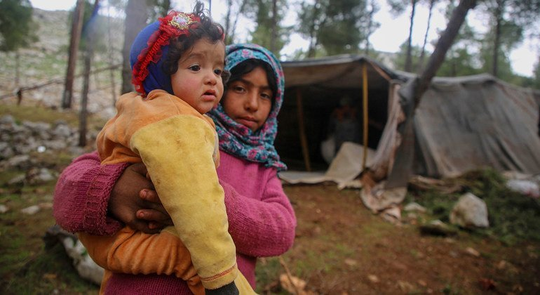 On 7 February 2020, a girl holds a younger child as children and families flee from southern Idlib and western Aleppo to the northern part of Idlib and Aleppo in Syria.