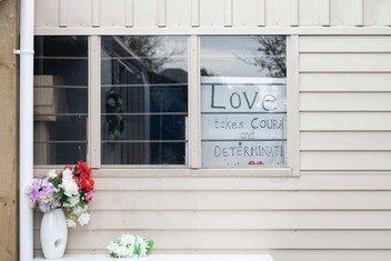 """在新西兰基督城一家伊斯兰中心的窗户上一块写有 """"爱需要勇气和决心 """"的牌子。"""