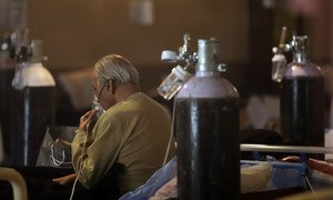 A patient receives oxygen treatment in a banquet hall, temporarily converted into a COVID-19 emergency ward in New Delhi, India.