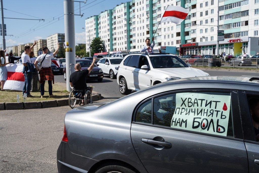 """Un panneau indiquant """"Arrêtez de nous blesser"""" sur la vitre d'une voiture à Minsk alors que des manifestants descendent dans les rues de la capitale du Belarus à la suite de l'élection présidentielle contestée."""