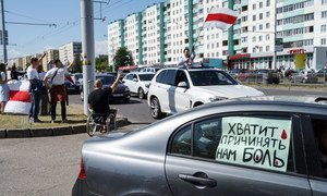A sign reads 'stop hurting us' as protesters take to the streets in the Belarusian capital, Minsk, over the disputed presidential election.