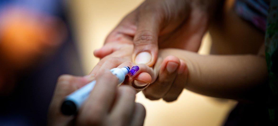पाकिस्तान के लाहौर में एक स्वास्थ्यकर्मी एक बच्चे की उँगली का निशान दिखाते हुए कि उस बच्चे को पोलियो से बचाने वाली दवा पिला दी गई है.