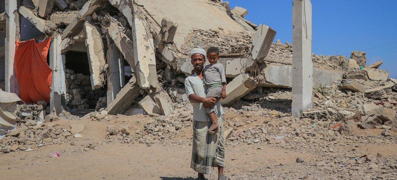 رجل يحمل طفله في مخيم الضالع للنازحين في اليمن.