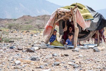 A displaced woman and her children in a makeshift shelter on the west coast of Yemen.